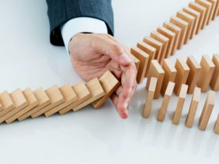 Businessman hand stopping falling blocks on table